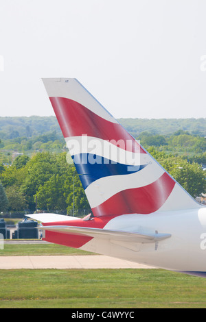 Tail fin of a BA jet taxiing at Gatwick airport, Sussex, UK - Stock Photo