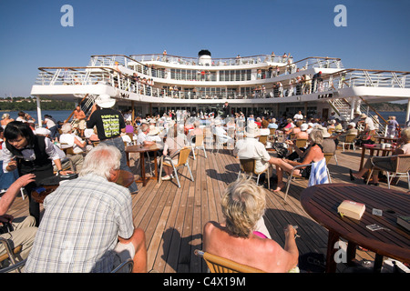 Passengers sitting on the lido deck of a cruise ship in the sunshine - Stock Photo