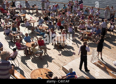 Passengers sitting on the lido deck of a cruise ship in the sunshine, listening to a singer - Stock Photo