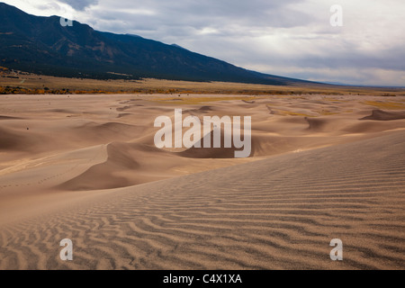 Panorama expansive rolling red Sand dunes footprints in abstract shapes, lines, patterns, tiny people for scale - Stock Photo