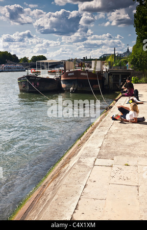 young woman female student in Paris France relaxing beside river Seine with book in sunshine river barges dramatic - Stock Photo