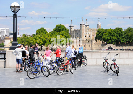 Group of tourists using hired bikes on escorted sightseeing trip listening to tour guide (in red) opposite the Tower - Stock Photo