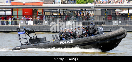 Metropolitan Police high speed Rigid Inflatable Boat and police team passing Tower Pier on River Thames - Stock Photo