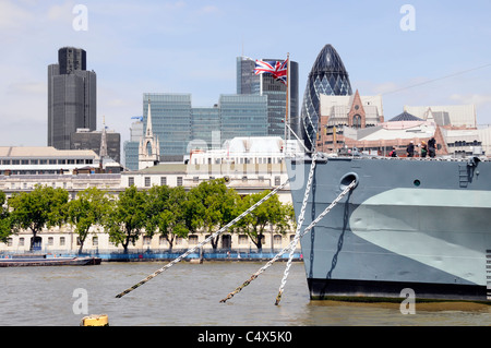 Union Jack flying on bow of historical HMS Belfast museum ship with City of London skyline of skyscraper landmark - Stock Photo