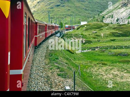 Rhatische Bahn train approaching Bernina Lagalp station en route to St. Moritz in Switzerland on the Bernina railway - Stock Photo