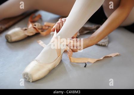 Female ballet dancer adjusting laces on her shoes - Stock Photo