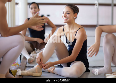 Female ballet dancer talking to friends and relaxing at school - Stock Photo