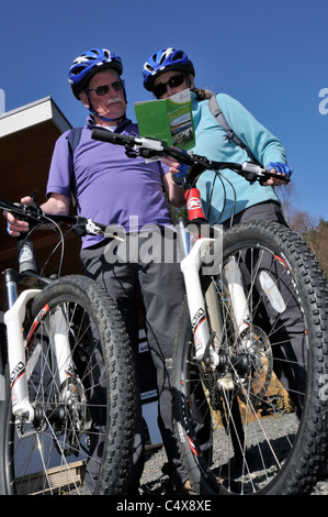 Cyclists choosing a cycle route in Kielder Water & Forest Park Northumberland, England, UK - Stock Photo