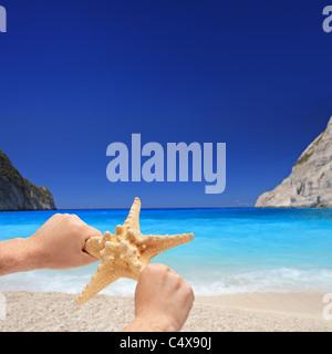 Person holding a starfish on a sandy beach on Zakynthos island - Stock Photo