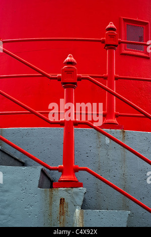 Abstract architectural detail photo of a set of concrete stairs with bright red railings against a bright red wall. - Stock Photo