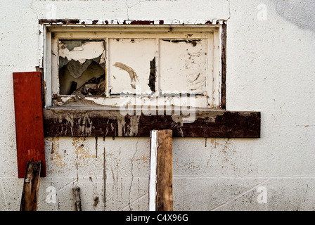 An old window on the white wall of a run-down building. - Stock Photo