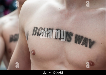 Men with gay pride message stencilled on their bare chests at the Christopher Street Day Parade in Berlin Germany - Stock Photo