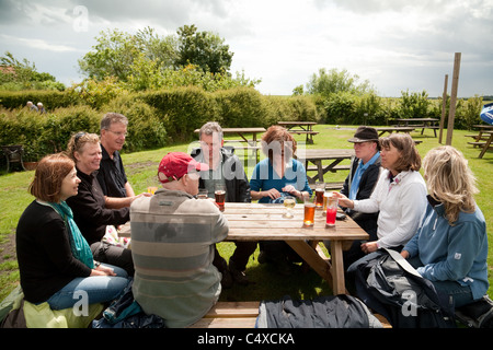 A group of people drinking in The Jolly Sailor pub beer garden, Orford, Suffolk UK - Stock Photo