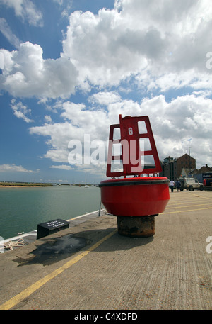 A port hand channel marker buoy stands on the quay at Wells-next-the-Sea, Norfolk waiting to be picked up and put - Stock Photo