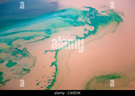 Silt ladden waters from a river mixing with the blue waters of Lake Bogoria. Kenya - Stock Photo
