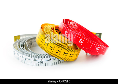 Three colorful measuring tapes coiled on white background - Stock Photo
