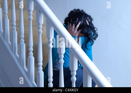 Young woman sitting alone on stairs hands on head. - Stock Photo