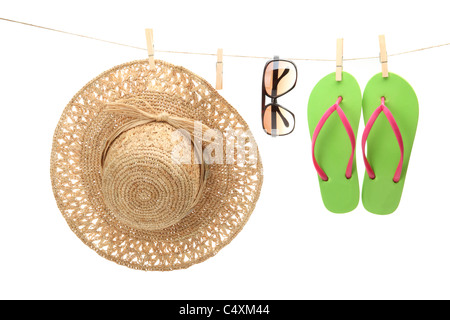 Straw hat,sunglasses and flip flops hanging on clothes line. - Stock Photo