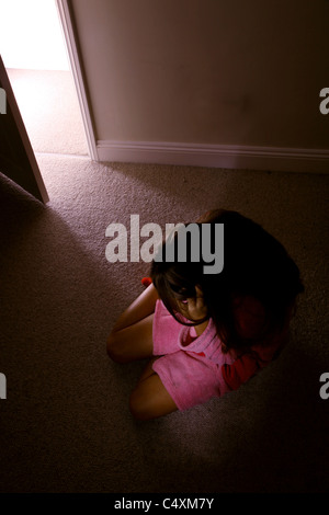 Young female sitting alone in a dark room wearing a pink dressing gown looking down. - Stock Photo