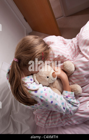 Young girl cuddling a teddy bear sitting on the bed, head down. - Stock Photo