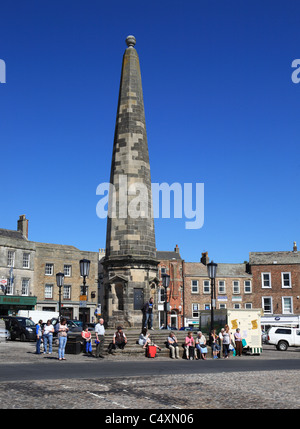 People sitting on the steps around the obelisk in Richmond's market place, North Yorkshire, England, UK - Stock Photo