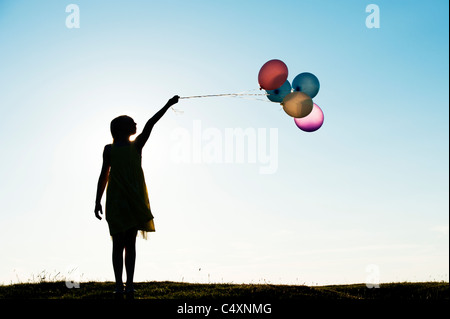 Silhouette of a young girl holding coloured balloons at sunset - Stock Photo