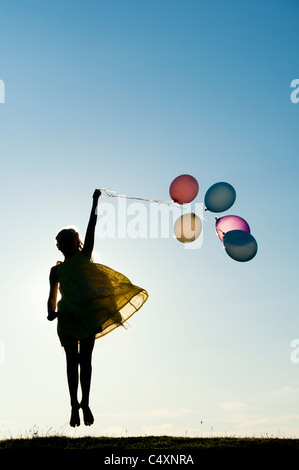 Silhouette of a young girl jumping with coloured balloons at sunset - Stock Photo