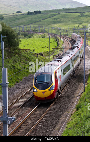 Power lines, and gantries for electric trains_British Railways _Virgin Pendolino Train at Shap. West Coast Line, - Stock Photo