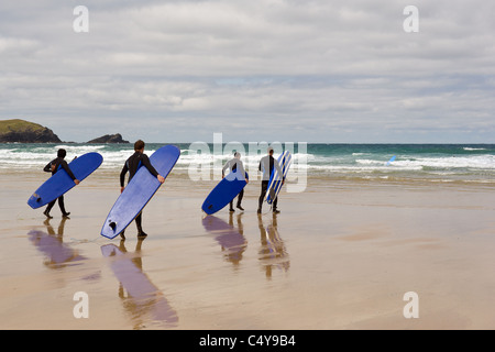 A group of surfers walking to the sea on Fistral Beach in Newquay. Cornwall. UK. - Stock Photo