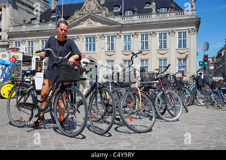 Young woman parking her bicycle in the busy Kongens Nytorv square in Copenhagen close to Nyhavn on a hot summer - Stock Photo