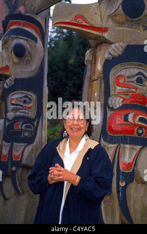 A Tlingit Native Alaskan and tribal elder describes her Indian people's totem poles in the village of Kake on Kupreanof - Stock Photo