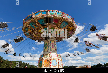 Chain carousel ride in an amusement parks carnivals or funfair UK England - Stock Photo