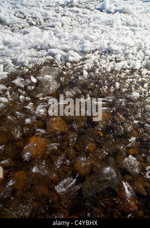 Blocks of melting ice slush float to the shore - Stock Photo