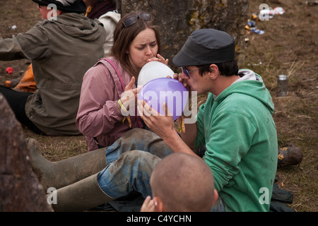 Couple breathing in balloons of nitrous oxide - laughing gas at the stone circle in Kings Meadow, Glastonbury Festival - Stock Photo