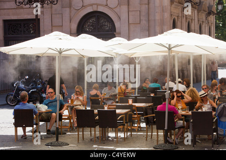 A pavement cafe is using mist sprayers to try to cool customers down in Seville Spain. - Stock Photo