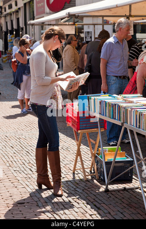Young woman looking at books in the Grote Markt or market place Haarlem, North Holland, Netherlands. JMH5056 - Stock Photo