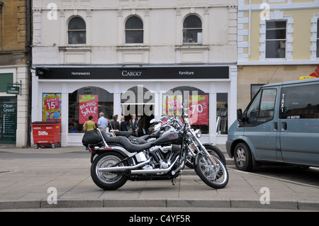 A pair of Harley Davidson motorbikes parked in the town center of cirencester gloucestershire - Stock Photo