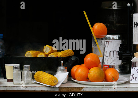 Grilled maize and fresh orange juice sold in a stall in the center of Prague, Czech Republic. - Stock Photo