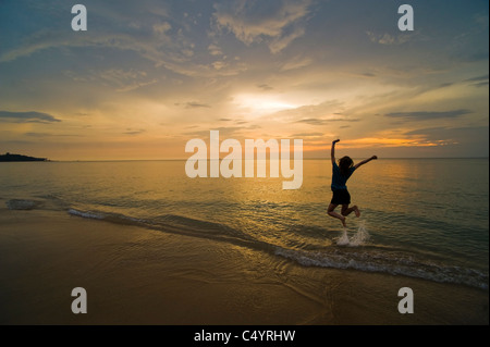 A young woman jumping for joy and celebrating on the beach at sunset. Taken on Phra Ae Beach, Koh Lanta, South Thailand - Stock Photo