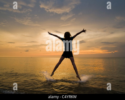 A young woman doing a star jump, jumping for joy and enjoying her freedom on the beach at sunset. - Stock Photo