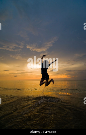 A young woman jumping for joy, celebrating on the beach at sunset. Taken on Phra Ae Beach, Koh Lanta, South Thailand - Stock Photo