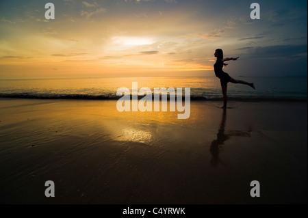 A young woman doing yoga exercises on the beach at sunset.Taken on Phra Ae Beach (Long Beach), Koh Lanta (Lanta - Stock Photo