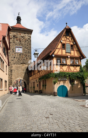 Cobbled street half timbered building by 14th century Siebersturm Siebers Tower gate. Rothenburg Ob der Tauber, - Stock Photo