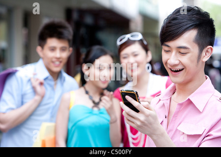 Young Man Using Phone In Front of Friends - Stock Photo