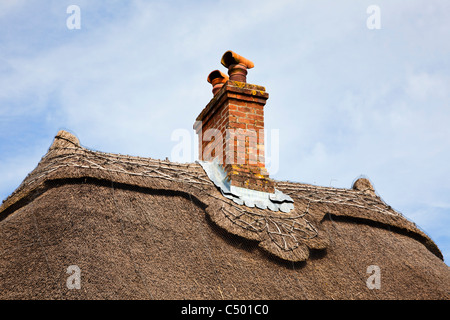 Thatched roof detail and chimney on a small old house England UK - Stock Photo