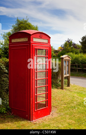 Traditional British red phone box and village noticeboard, England, UK - Stock Photo