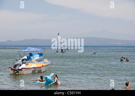 Children play in the water of the Jaltemba Bay in front of anchored sport fishing boats while frigate birds fly - Stock Photo