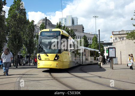 A tram passing Piccadilly Gardens in the centre of Manchester. - Stock Photo