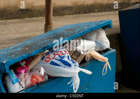 Litter bin overflowing with rubbish. - Stock Photo