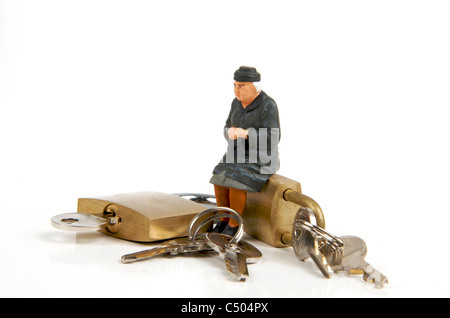 Miniature figurine of elderly lady sitting on padlocks - retirement / security / housing concept - Stock Photo